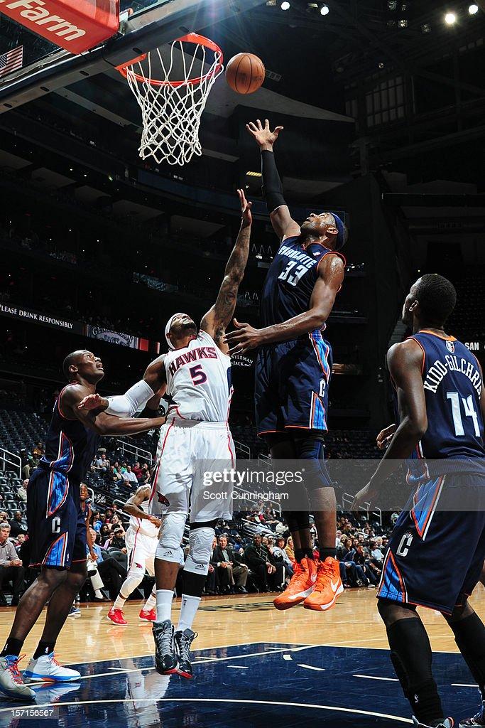 Brendan Haywood #33 of the Charlotte Bobcats shoots the ball against Josh Smith #5 of the Atlanta Hawks at Philips Arena on November 28, 2012 in Atlanta, Georgia.