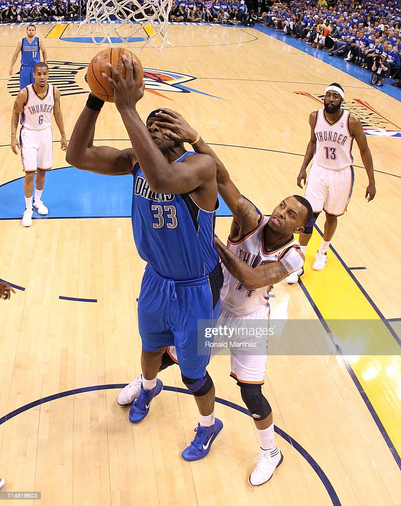 Brendan Haywood #33 of the Dallas Mavericks goes up for a shot as Daequan Cook #14 of the Oklahoma City Thunder grabs his face in Game Three of the Western Conference Finals during the 2011 NBA Playoffs at Oklahoma City Arena on May 21, 2011 in Oklahoma City, Oklahoma.