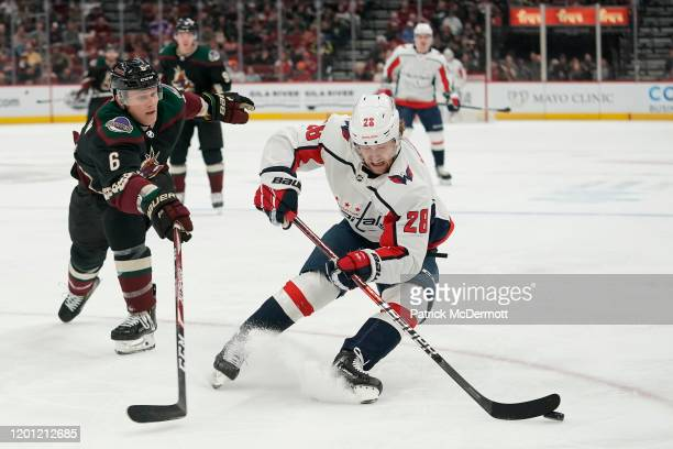 Brendan Leipsic of the Washington Capitals skates with the puck against Jakob Chychrun of the Arizona Coyotes in the first period at Gila River Arena...