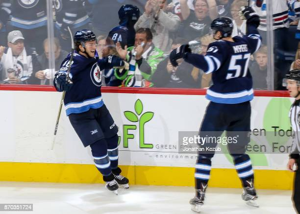 Brendan Lemieux and Tyler Myers of the Winnipeg Jets celebrate a third period goal against the Pittsburgh Penguins at the Bell MTS Place on October...