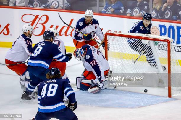 Brendan Lemieux Andrew Copp and Mason Appleton of the Winnipeg Jets watch as the puck trickles over the line past goaltender Sergei Bobrovsky of the...