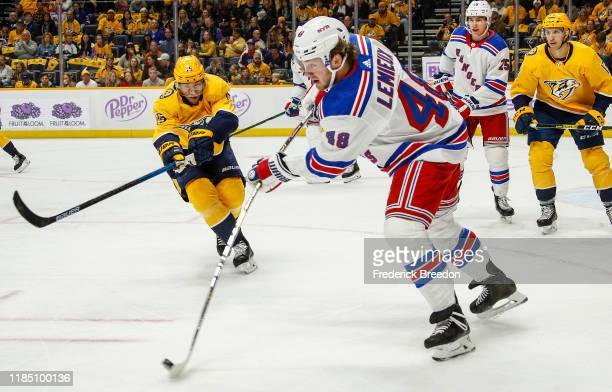 NASHVILLE TENNESSEE NOVEMBER Brendan Lemieux of the New York Rangers flips a puck past Craig Smith of the Nashville Predators during the first period...