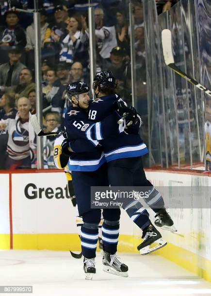 Brendan Lemieux of the Winnipeg Jets celebrates his first career NHL goal against the Pittsburgh Penguins with teammate Tyler Myers during the third...