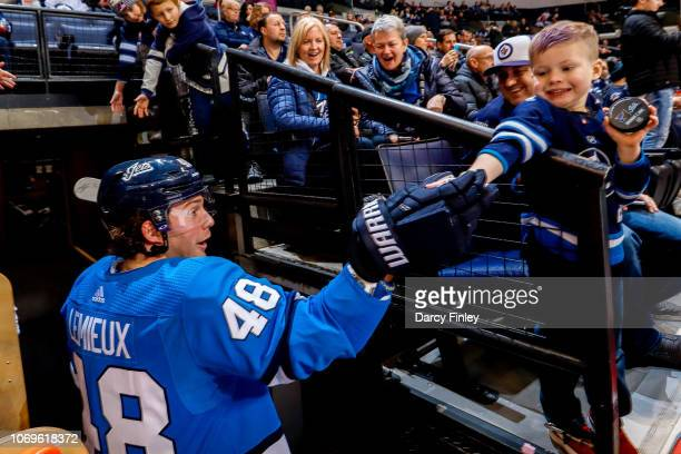 Brendan Lemieux of the Winnipeg Jets fist bumps a fan as he leaves the ice following the pregame warm up prior to NHL action against the St Louis...