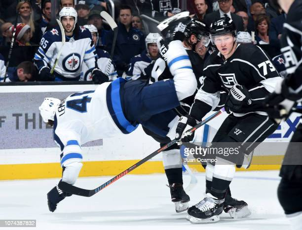 Brendan Lemieux of the Winnipeg Jets goes airborne after colliding with Adrian Kempe and Tyler Toffoli of the Los Angeles Kings during the second...