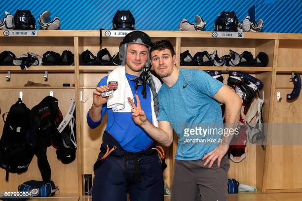 Brendan Lemieux of the Winnipeg Jets poses with teammate Mark Scheifele after scoring his first career NHL goal against the Pittsburgh Penguins at...