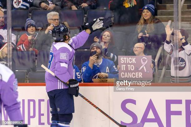 Brendan Lemieux of the Winnipeg Jets throws a puck over the glass to a young fan during the pregame warm up prior to NHL action against the Chicago...
