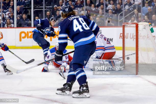 Brendan Lemieux of the Winnipeg Jets watches as teammate Andrew Copp shoots the puck past goaltender Henrik Lundqvist of the New York Rangers for a...