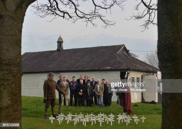 Brendan MacQuaile wearing a WWI uniform and piper John Lamb surrounded by relatives of Irish war dead and campaigners seek to preserve one of the...
