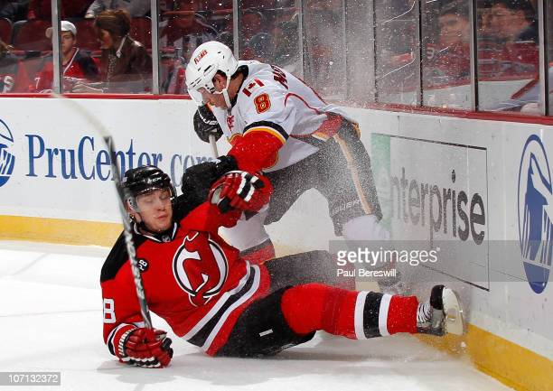Brendan Morrison of the Calgary Flames takes a tripping penalty as he trips Anton Volchenkov of the New Jersey Devils during the first period of a...
