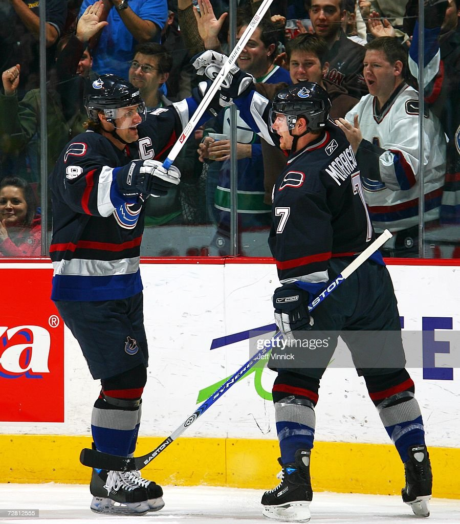 Brendan Morrison #7 of the Vancouver Canucks is congratulated by teammate Markus Naslund #19 after scoring against the Phoenix Coyotes at General Motors Place December 12, 2006 in Vancouver, Canada.