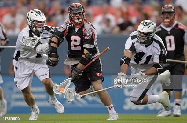 Brendan Mundorf of the Denver Outlaws controls the ball against the defense of Dan Cocchi and Nicky Polanco of the Long Island Lizards during Major...