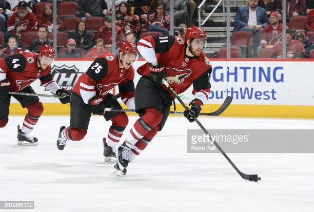 Brendan Perlini of the Arizona Coyotes advances the puck up ice against the Columbus Blue Jackets ahead of teammates Nick Cousins and Kevin...