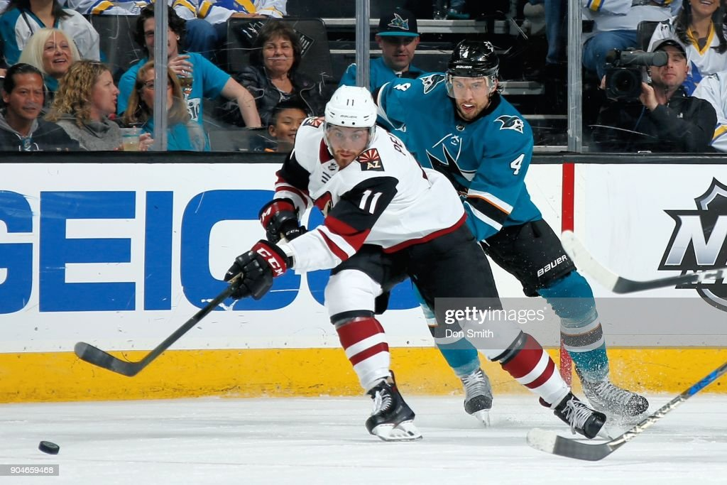 Brendan Perlini #11 of the Arizona Coyotes and Brenden Dillon #4 of the San Jose Sharks chase the puck at SAP Center on January 13, 2018 in San Jose, California.