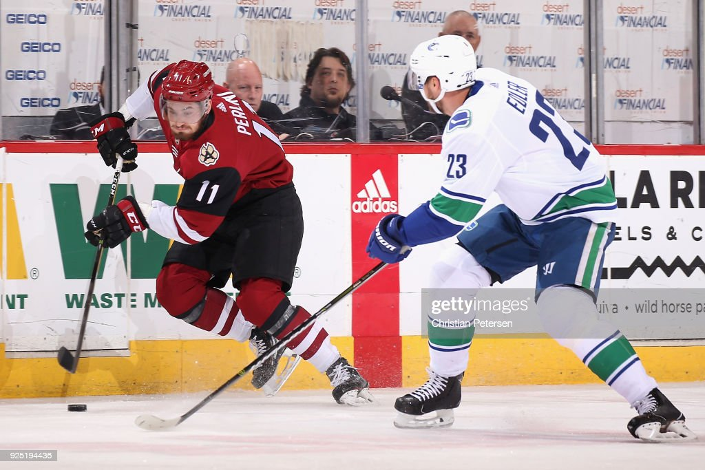 Brendan Perlini #11 of the Arizona Coyotes skates the puck past Alexander Edler #23 of the Vancouver Canucks during the first period of the NHL game at Gila River Arena on February 25, 2018 in Glendale, Arizona. The Canucks defeated the Coyotes 3-1