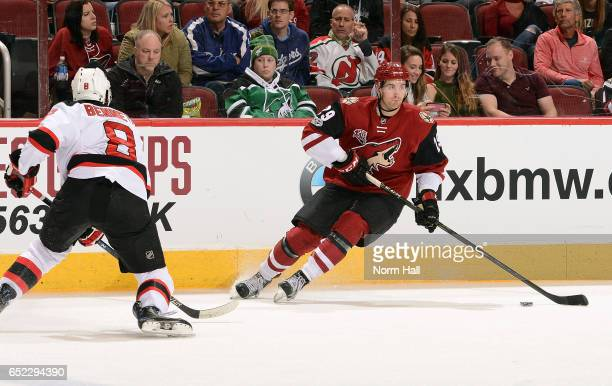 Brendan Perlini of the Arizona Coyotes skates with the puck as Beau Bennett of the New Jersey Devils defends during the third period at Gila River...