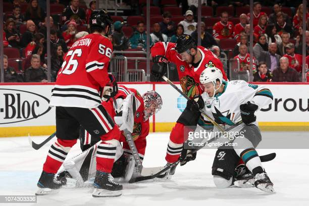 Brendan Perlini of the Chicago Blackhawks ans Kevin Labanc of the San Jose Sharks battle for the puck in front of goalie Cam Ward in the third period...