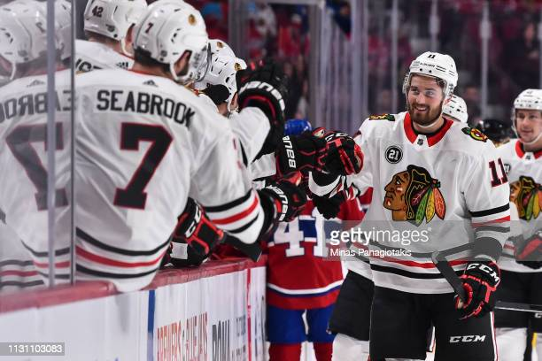 Brendan Perlini of the Chicago Blackhawks celebrates a third period goal with teammates on the bench against the Montreal Canadiens during the NHL...
