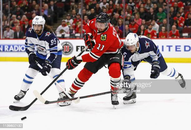 Brendan Perlini of the Chicago Blackhawks is pressured by Mathieu Perreault and Dmitry Kulikov of the Winnipeg Jets at the United Center on April 01...