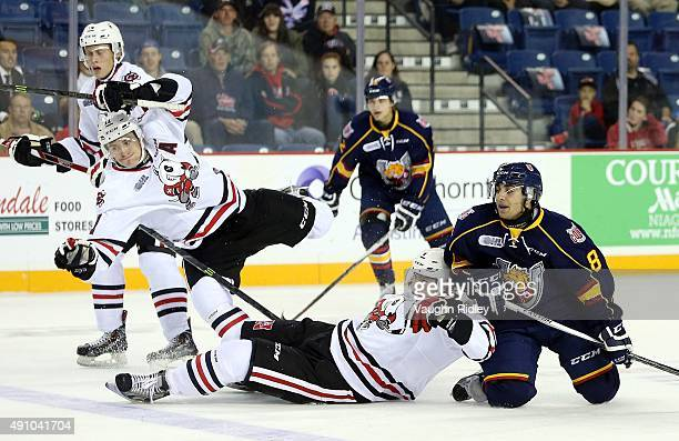 Brendan Perlini of the Niagara IceDogs trips over teammate Vince Dunn and Lucas Chiodo of the Barrie Colts as they battle for the puck during an OHL...