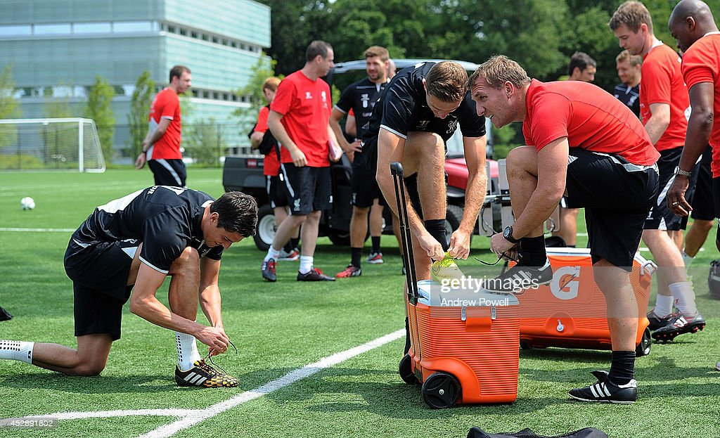 Brendan Rodgers manager of Liverpool boots up next to Jordan Henderson and Martin Kelly before a training session at Princeton University on July 29, 2014 in Princeton, New Jersey.