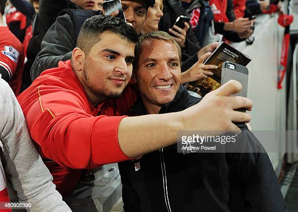 Brendan Rodgers manager of Liverpool gets a selfie with a fan at the end of a training session at Suncorp Stadium on July 16, 2015 in Brisbane,...