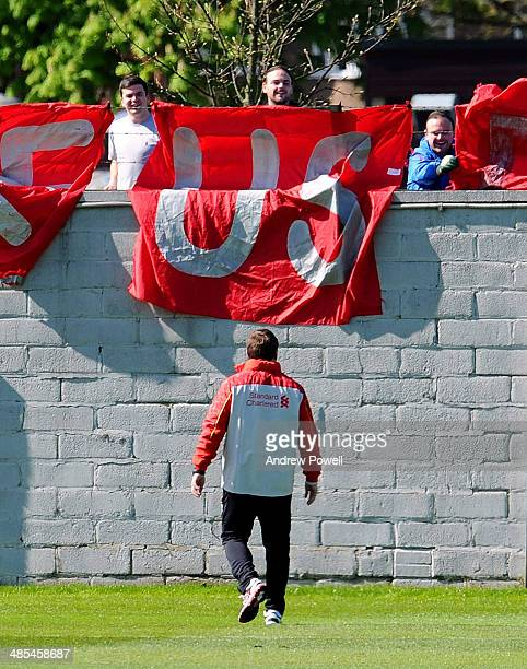 Brendan Rodgers manager of Liverpool speaks with fans who have displayed a banner with the message 'Make Us Dream' during a training session at...