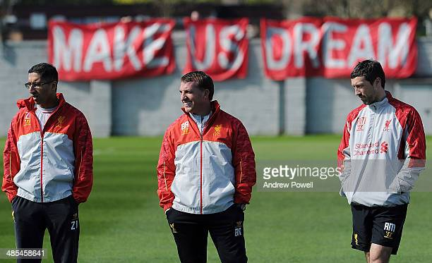 Brendan Rodgers manager of Liverpool stands next to Zaf Iqbal first team doctor and Ryland Morgans Head of Fitness and Conditioning as Liverpool fans...