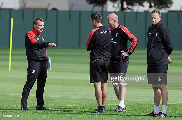 Brendan Rodgers manager of Liverpool talks with Gary McAllister first team coach Chris Davies head of opposition analysis and Pepijn Lijnders first...
