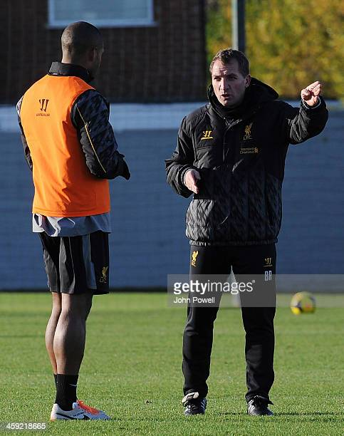 Brendan Rodgers manager of Liverpool talks with Glen Johnson during a training session at Melwood Training Ground on December 24 2013 in Liverpool...