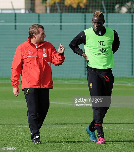 Brendan Rodgers manager of Liverpool talks with Mario Balotelli during a training session at Melwood Training Ground on October 17 2014 in Liverpool...