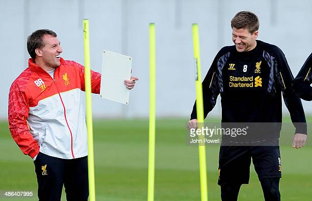 Brendan Rodgers mangaer of Liverpool laughs with Steven Gerrard during a training session at Melwood Training Ground on April 24 2014 in Liverpool...