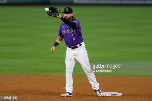 Brendan Rodgers of the Colorado Rockies catches the ball while warming up during the eighth inning against the Houston Astros at Coors Field on...