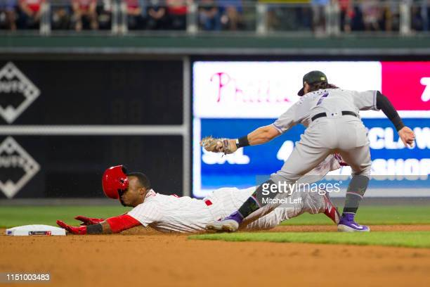 Brendan Rodgers of the Colorado Rockies tags out Jean Segura of the Philadelphia Phillies trying to steal second base in the bottom of the second...