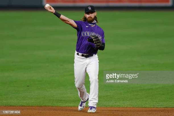 Brendan Rodgers of the Colorado Rockies throws the ball to first while warming up during the eighth inning against the Houston Astros at Coors Field...