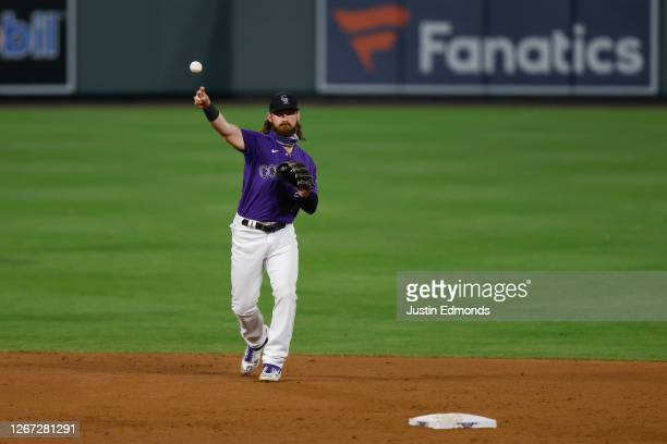 Brendan Rodgers of the Colorado Rockies throws to first while warming up during the ninth inning against the Houston Astros at Coors Field on August...