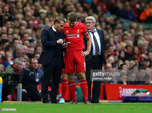 Brendan Rodgers the head coach / manager of Liverpool discusses tactics with Steven Gerrard of Liverpool