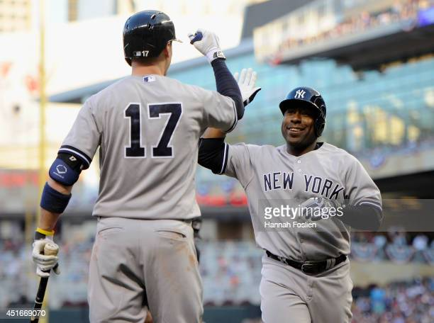 Brendan Ryan of the New York Yankees congratulates teammate Zelous Wheeler on hitting a solo home run against the Minnesota Twins in his major league...