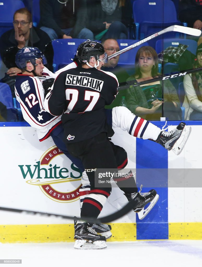 Brendan Semchuk #27 of the Vancouver Giants checks Jordan Topping #12 of the Tri-City Americans during the third period of their WHL game at the Langley Events Centre on October 6, 2017 in Langley, British Columbia, Canada.
