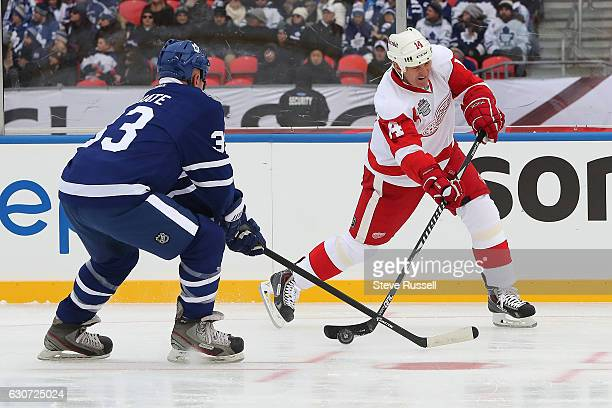 TORONTO ON DECEMBER 31 Brendan Shanahan fires a shot at the net as Al Iafrate tries to block it as the Toronto Maple Leafs alumni play the Detroit...