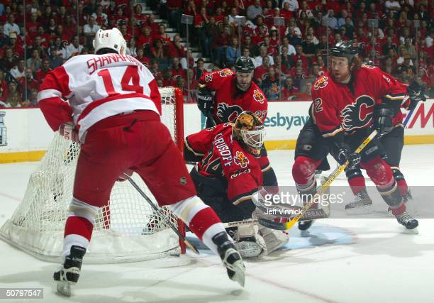 Brendan Shanahan of the Detroit Red Wing tries to stuff the puck into the short side of the net behind Miikka Kiprusoff of the Calgary Flames as...