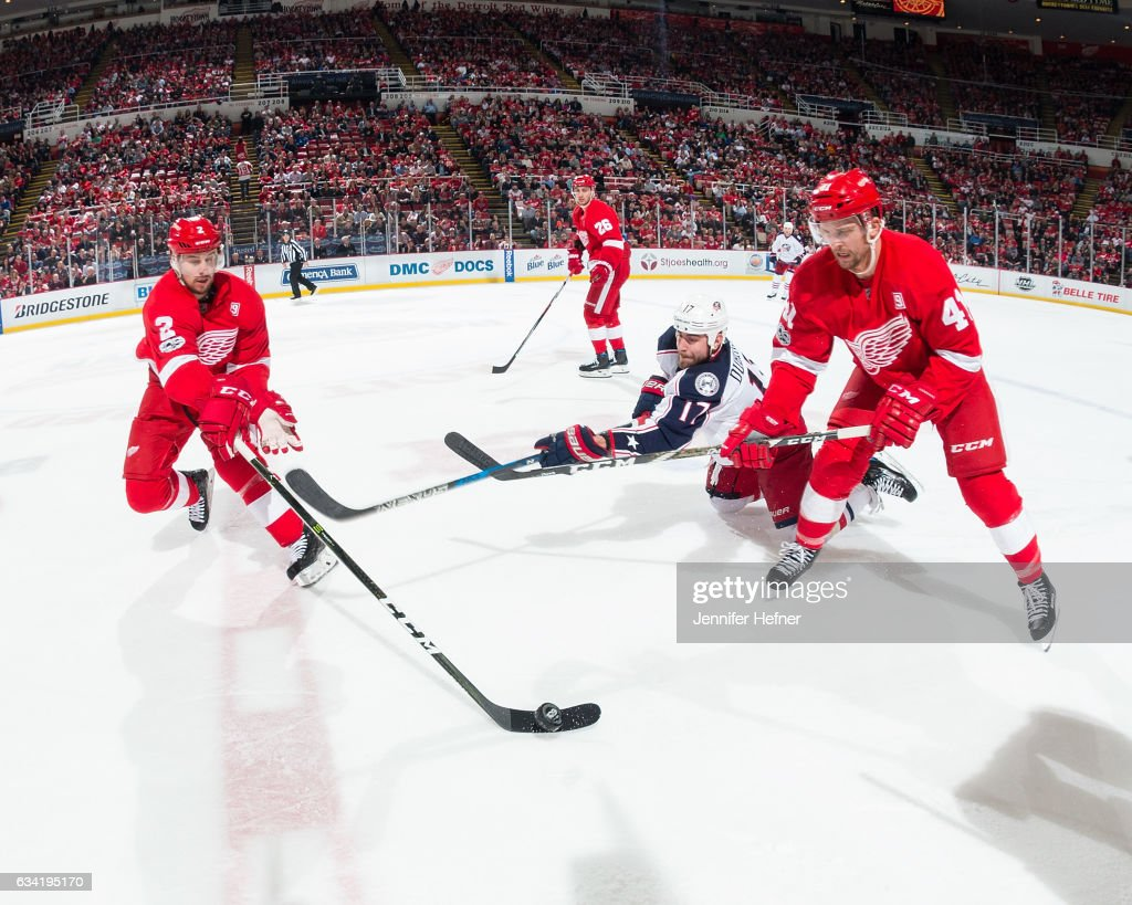Brendan Smith #2 and Luke Glendening #41 of the Detroit Red Wings battle for the puck with Brandon Dubinsky #17 of the Columbus Blue Jackets during an NHL game at Joe Louis Arena on February 7, 2017 in Detroit, Michigan. The Blue Jackets defeated the Wings 3-2 in OT.