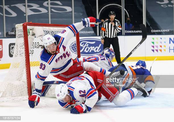 Brendan Smith and Mika Zibanejad of the New York Rangers fall defending against Anthony Beauvillier of the New York Islanders during the second...