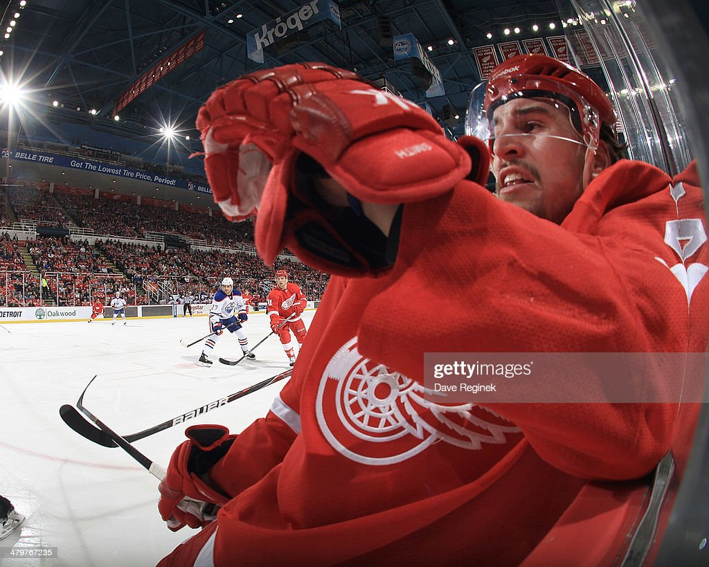 Brendan Smith #2 of the Detroit Red Wings is checked off the puck in the corner during an NHL game against the Edmonton Oilers on March 14, 2014 at Joe Louis Arena in Detroit, Michigan. Detroit defeated Edmonton 2-1 in a shootout