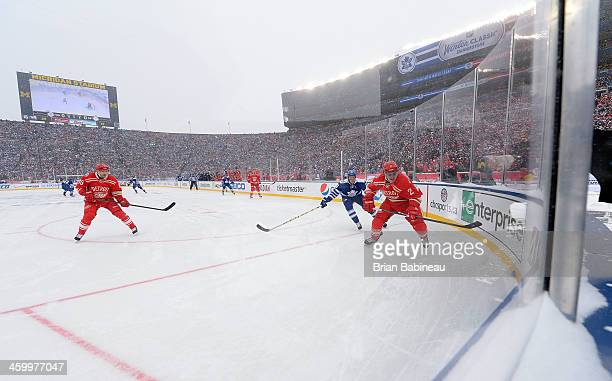 Brendan Smith of the Detroit Red Wings skates after the puck while under pressure from James van Riemsdyk of the Toronto Maple Leafs as Pavel Datsyuk...