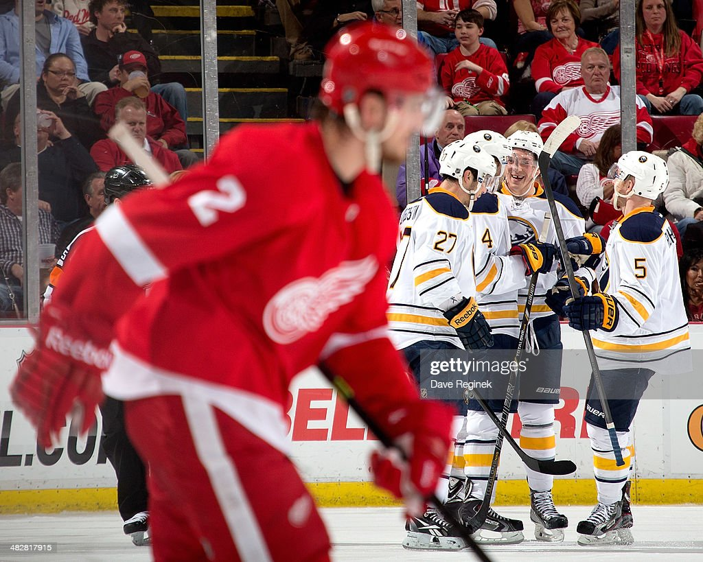 Brendan Smith #2 of the Detroit Red Wings skates out of the penalty box as Matt D'Agostini #27, Luke Adam #72 and Chad Ruhwedel #5 of the Buffalo Sabres congratulate teammate Jamie McBain #4 after scoring a power-play goal during an NHL game on April 4, 2014 at Joe Louis Arena in Detroit, Michigan.