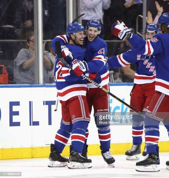 Brendan Smith of the New York Rangers celebrates his empty net goal at 19:43 of the third period against the Winnipeg Jets and is joined by Brett...
