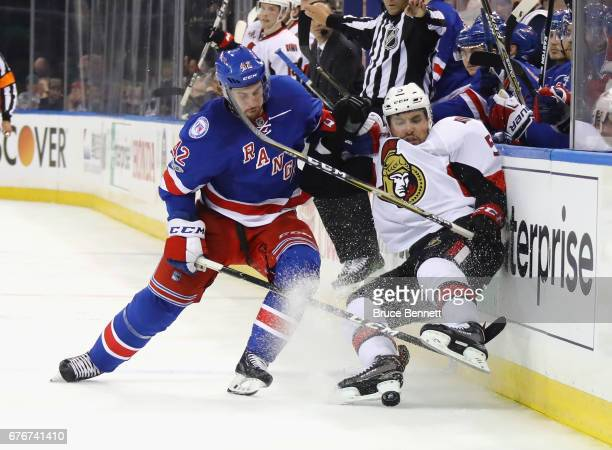 Brendan Smith of the New York Rangers checks Cody Ceci of the Ottawa Senators into the boards during the third period in Game Three of the Eastern...