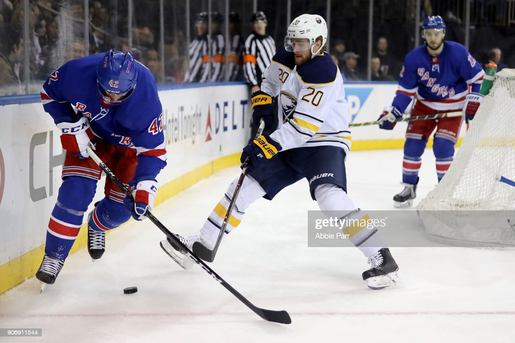 Brendan Smith #42 of the New York Rangers fights for the puck against Scott Wilson #20 of the Buffalo Sabres in the third period during their game at Madison Square Garden on January 18, 2018 in New York City.