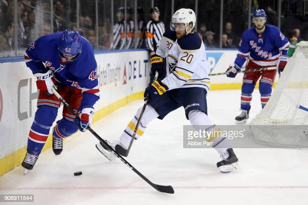 Brendan Smith of the New York Rangers fights for the puck against Scott Wilson of the Buffalo Sabres in the third period during their game at Madison...